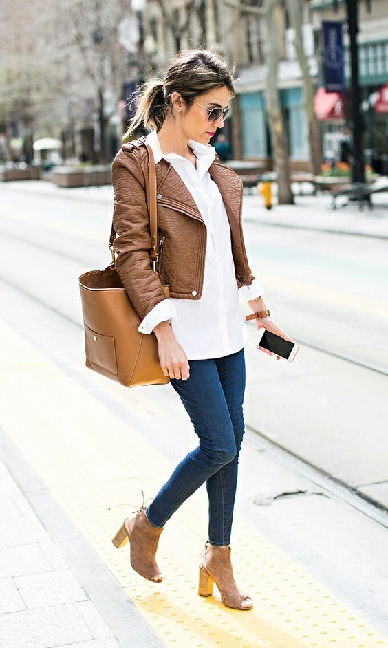 a white shirt, a cropped brown jacket, blue skinnies, brown booties and a bag