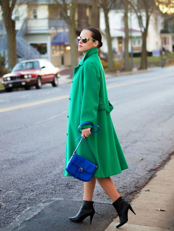 an emerald coat, black booties and a bright blue bag for a super bold look