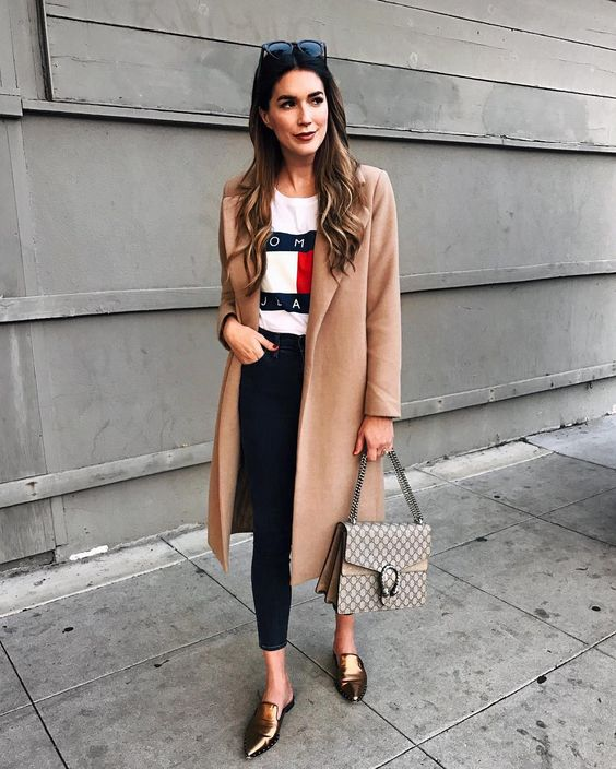 navy cropped skinnies, metallic flats, a printed logo tee, a camel coat and a bag