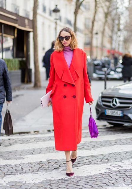 a bright coral oversize coat, burgundy shoes, a pink turtleneck and a pink bag