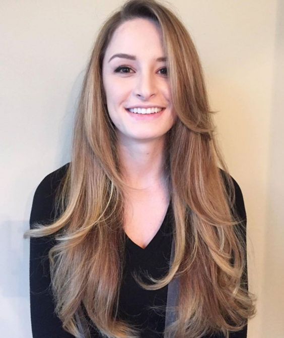 a long layered haircut with side bangs and  blonde balayage for a chic look