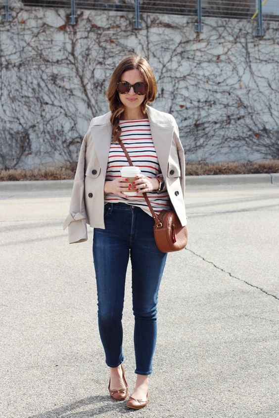 navy skinnies, a striped colorful top, brown flats and a bag, a grey cropped trench