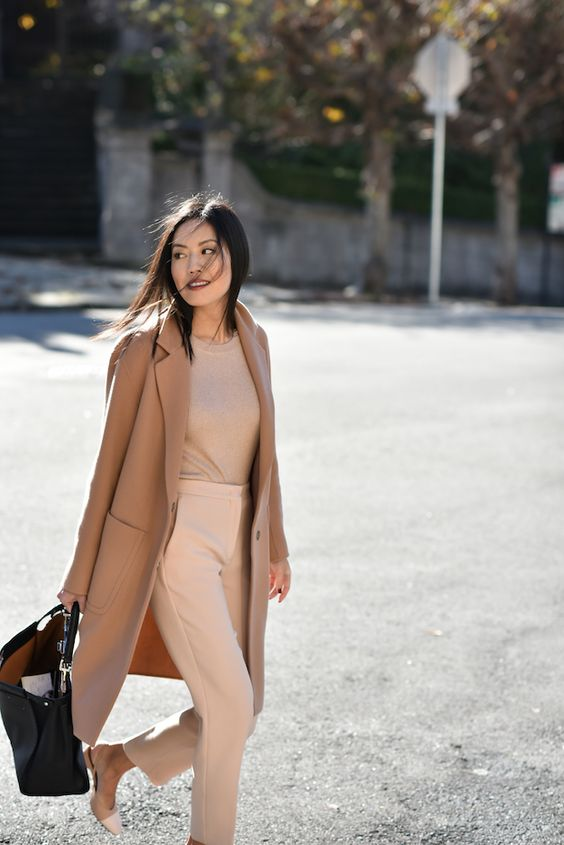two tone flats, blush pants, a neutral top, a camel coat and a blakc bag for work