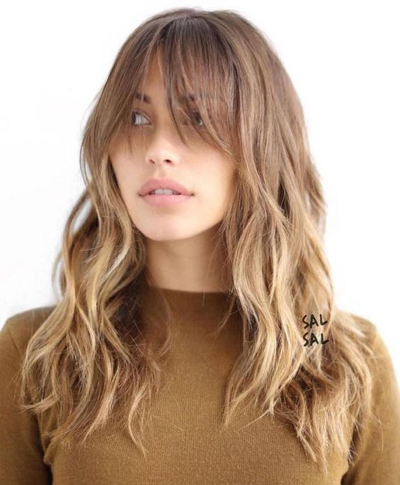 a long lyered haircut with a light ombre and long bangs plus messy waves
