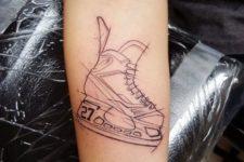Black-contour skates tattoo on the forearm