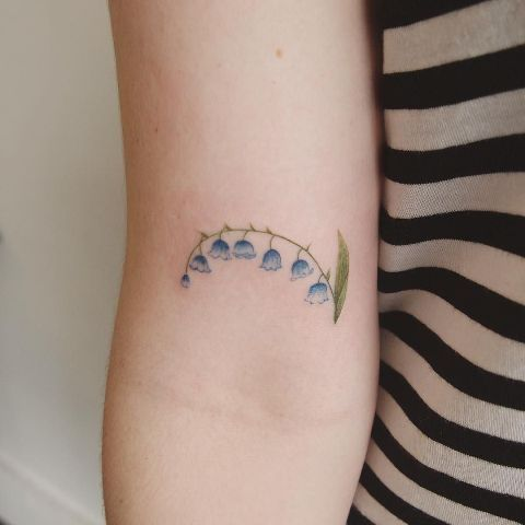 Blue and green tattoo on the arm