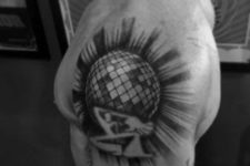 Disco ball and dancing people tattoo on the shoulder