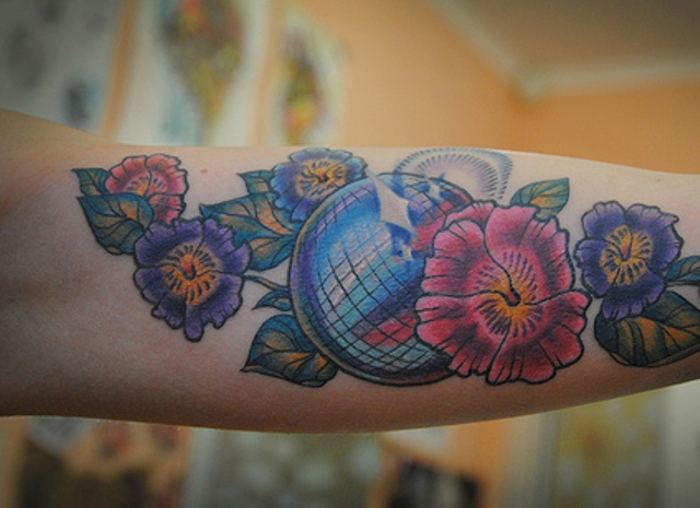Disco ball and flowers tattoo on the forearm