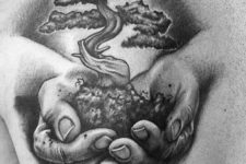 Hands holding tree of life tattoo
