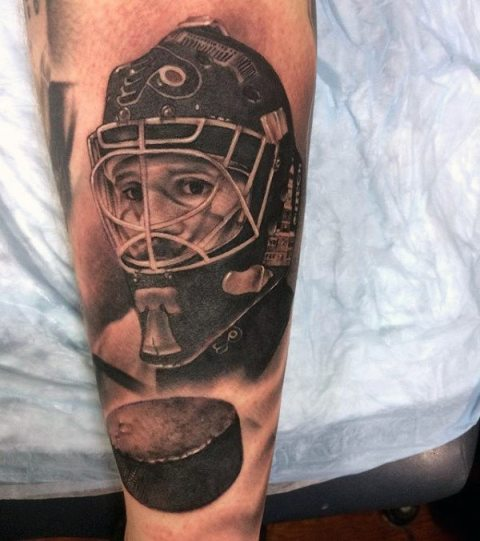 Hockey player and hockey puck tattoo