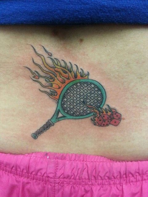 Racket and flames tattoo on the low back