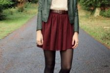 With beige shirt, leather jacket, belt and lace up boots