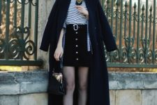 With black cap, striped shirt, black midi coat, metallic bag and ankle boots