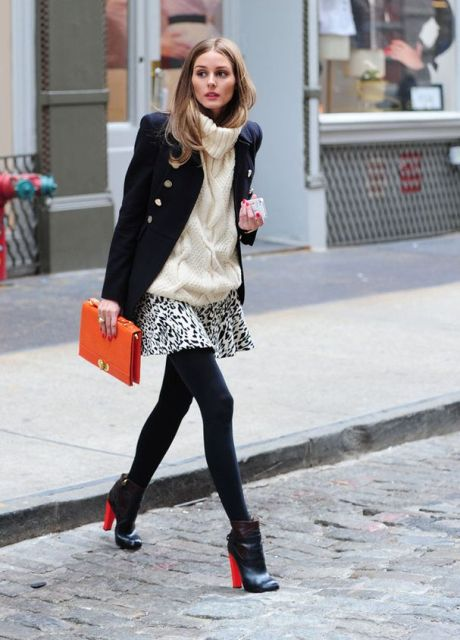 With black coat, white sweater, black and red boots and orange clutch
