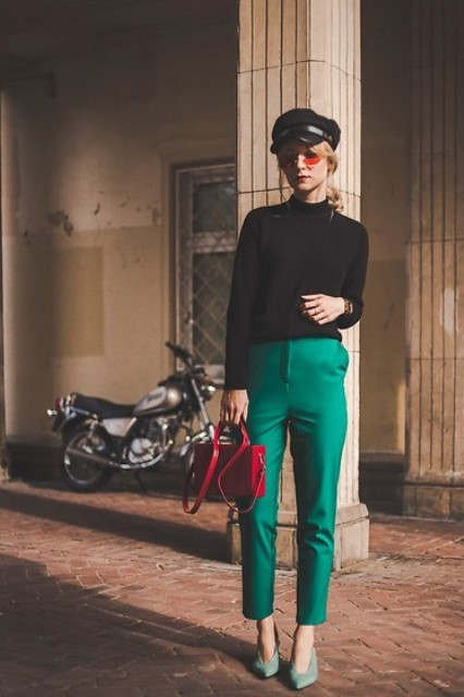 With black turtleneck, cap, emerald trousers and red bag