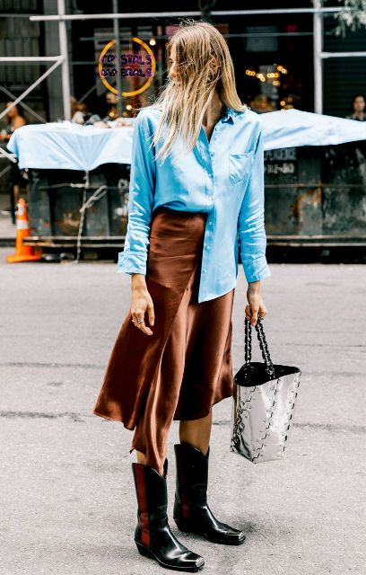 With blue button down shirt, black high boots and metallic tote