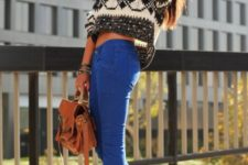 With blue pants, lace up boots and brown bag