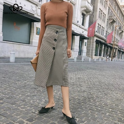 With brown shirt, leather clutch and black mules