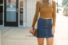 With denim skirt, white and black sneakers and small bag