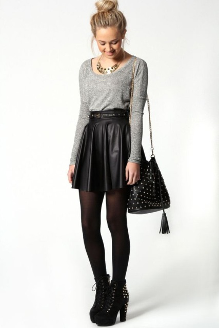 With gray shirt, black tights, black embellished boots and bag