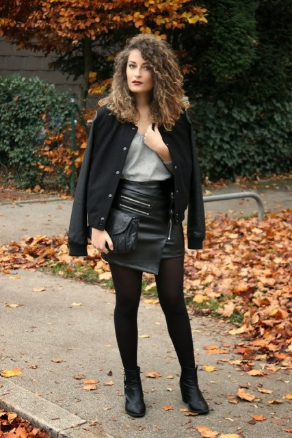 With gray t shirt, black bomber jacket, black clutch and boots