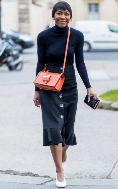 With navy blue turtleneck, trumpet skirt and orange bag