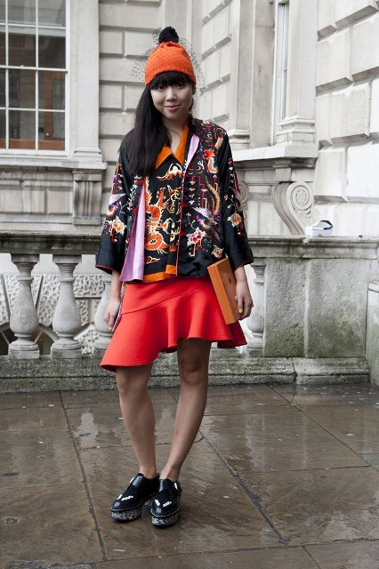With orange hat, platform shoes, unique clutch and printed jacket