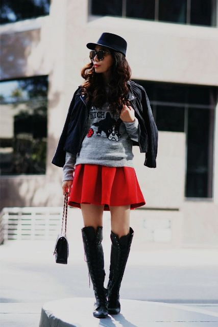 With printed sweatshirt, black high boots, black cap, black leather jacket and small bag