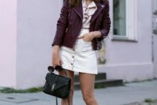 With ruffled blouse, leather jacket, lace up shoes and small bag
