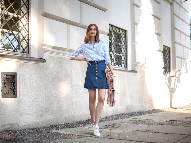 With striped shirt, white sneakers and pale pink fringe bag