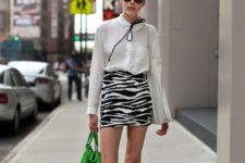 With white blouse, green bag and black flat shoes
