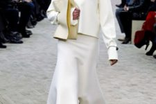 With white loose sweatshirt, beige clutch and gray boots