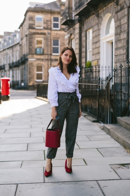 With white ruffled blouse, high-waisted trousers and red bag