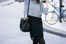 With wide brim hat, black skirt, ankle boots and black bag