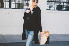distressed jeans, a black t-shirt, white sneakers, a black long cardigan and a faux fur clutch
