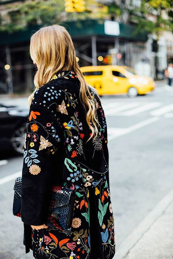 a black coat with flora and fauna embroidery in bright colors for making a statement