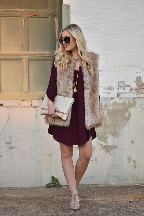 a chiffon burgundy over the knee dress, grey shoes, a faux fur waistcoat, a neutral clutch bag