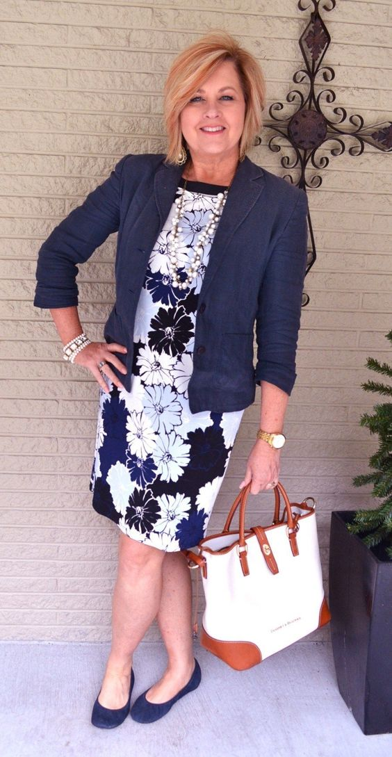 a floral sheath dress, a navy blazer, navy flats and a brigth bag plus a pearl necklace