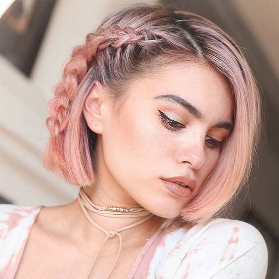 a short rose gold bob with a small side braid for a chic and trendy boho feel