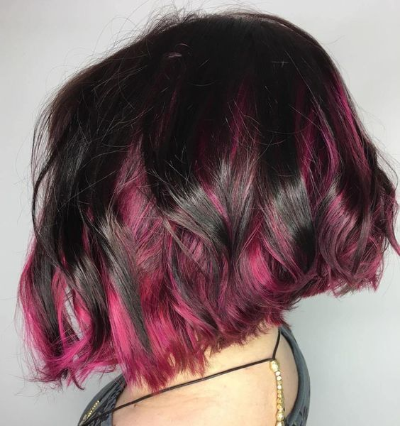 a black wavy angled bob with hot pink peekaboo highlights looks super contrasting