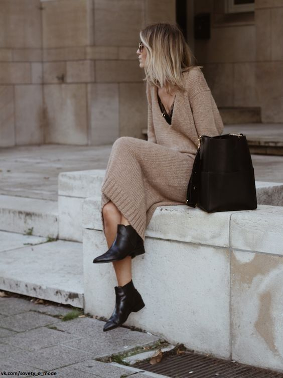 a camel knit midi dress with a black top underneath, black booties and a black bag