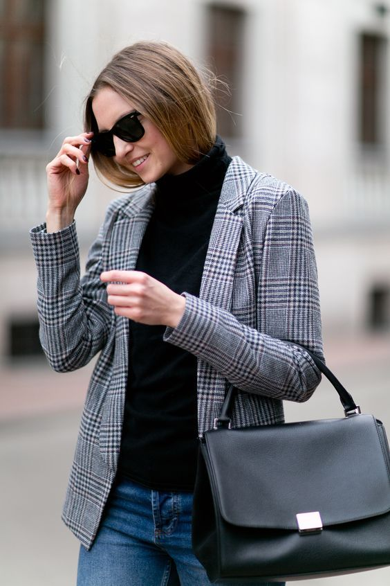 a casual work look with a blakc turtleneck, a checked jacket, blue jeans and a black bag