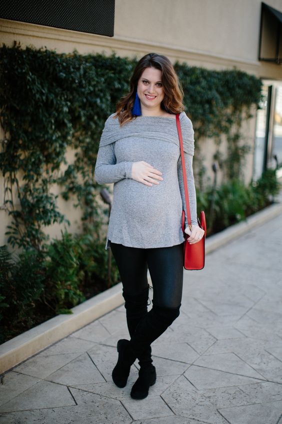 a grey off the shoulder sweater, black leggings, black boots and a red bag plus blue earrings
