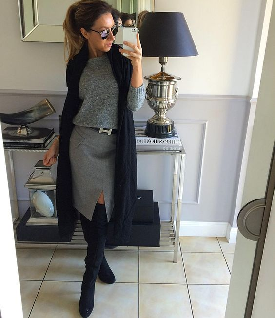 a grey skirt with a front slit, a grey sweater, a navy scarf, navy tall boots for a chic look