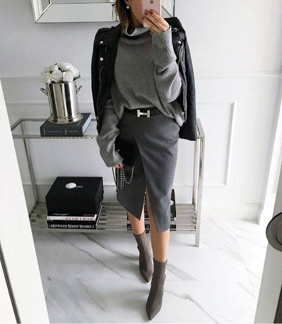 a monochromatic look with a grey wrap pencil skirt, a grey oversized sweater, grey socks, boots and a black leather jacket