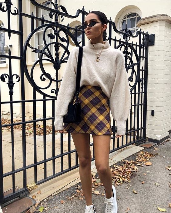 a neutral oversized cashmere sweater, a bright plaid mini skirt, white sneakers and a black bag