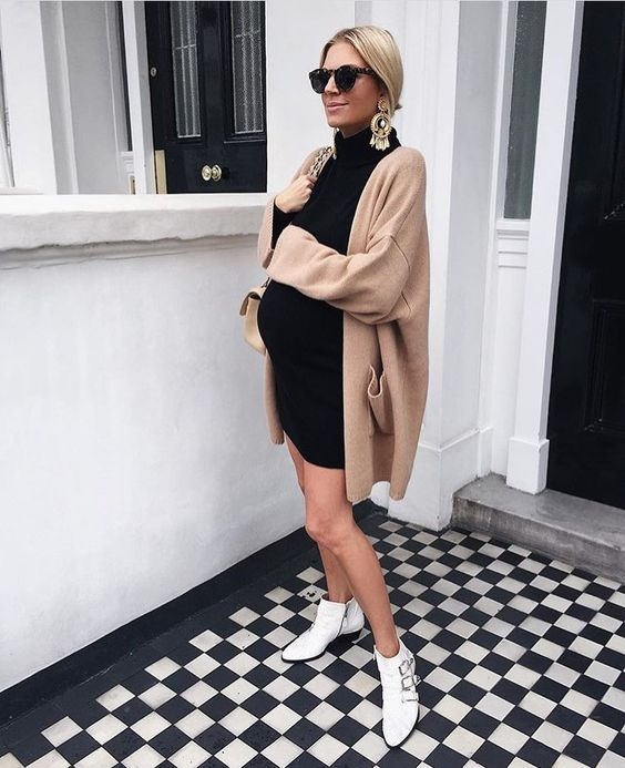 a black turtleneck dress, a camel cardigan, white booties and statement earrings for maximal comfort