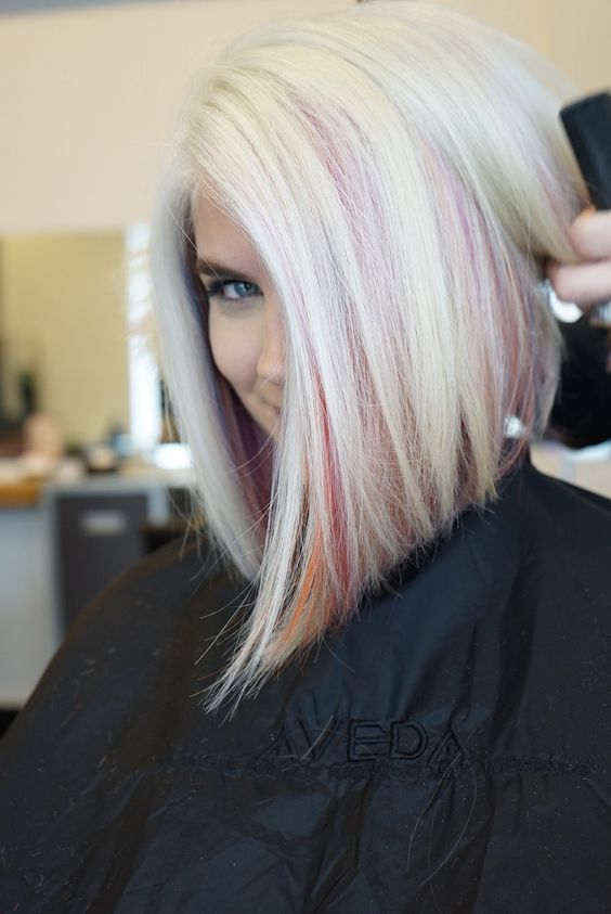 a long angled icy blonde bob with pink and orange peekaboo highlights for a plyaful touch