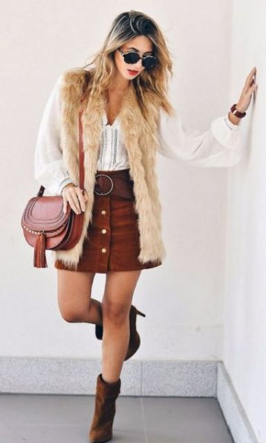 a white boho shirt, a rust mini skirt with buttons, brown booties, a saddle bag and a neutral fur waistcoat