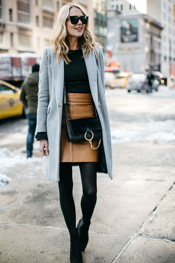 a black sweater, a brown leather skirt, a grey coat and black booties for office